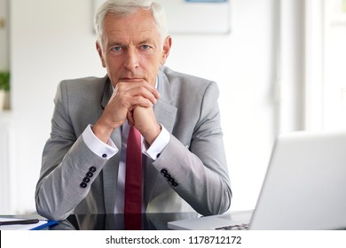 Portrait of thinking senior businessman wearing suit and looking at camera while sitting at office desk.
