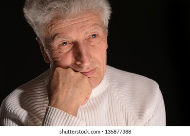 portrait of a  thinking senior man  over a black  background