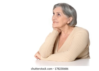 Portrait of thinking and smiling elderly woman on white background