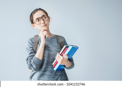 Portrait of thinking student girl on grey background