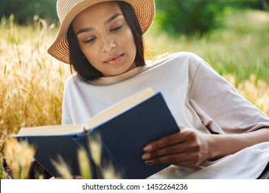 Portrait of thinking woman wearing lip piercing and straw hat reading book while lying on grass in green park