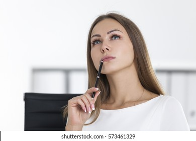 Portrait of a thinking woman wearing white clothes and looking upwards  thinking about current task