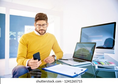 Portrait of thinking young businessman using his mobile phone and text messaging while sitting at office desk.