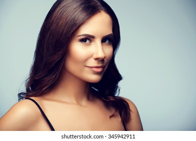 portrait of thinking young woman in black tank top clothing, on grey background