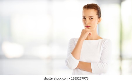 Portrait of a thinking young woman standing indoor.