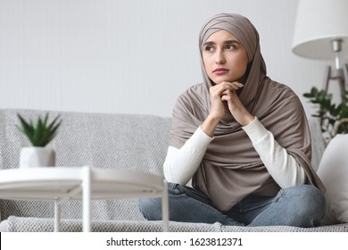 Portrait of thoughtful arabic woman in hijab sitting on couch at home, resting head on hands and looking away with sad face expression, copy space
