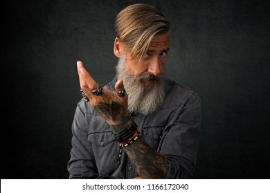 Portrait of a thoughtful bearded man who make a gesture with his left hand