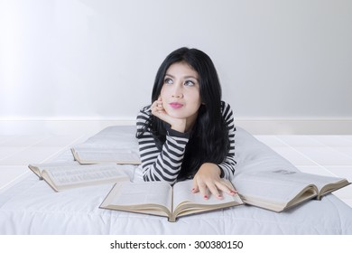 Portrait of thoughtful beautiful woman lying on the bed while reading books and imagine something