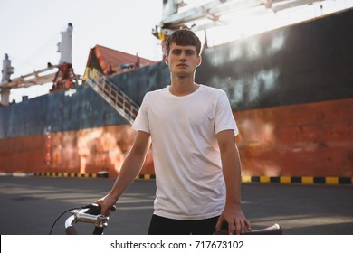 Portrait of thoughtful boy with brown hair standing with bicycle and dreamily looking in camera. Young man in white t-shirt standing and posing on camera with big ship on background