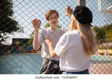 Portrait of thoughtful boy standing on basketball court and dreamily looking at pretty girl with blond hair through mesh fence. Young beautiful couple standing and looking on each other