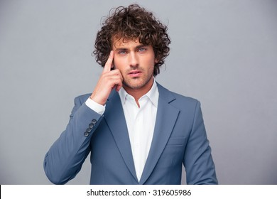 Portrait of thoughtful businessman looking at camera over gray background