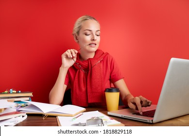 portrait of thoughtful caucasian female at work place, she is contemplation, having too much work, deadlines. sit with laptop isolated over red background