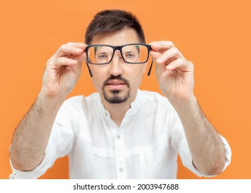 Portrait of thoughtful caucasian man holding eye glasses outstretched and looking through it while standing against color background. Now I can see you well.