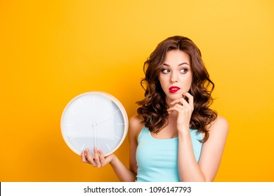 Portrait of thoughtful confused girl holding hand on chin looking to the side away biting lip having round clock at hand showing o-clock planning time isolated on yellow background