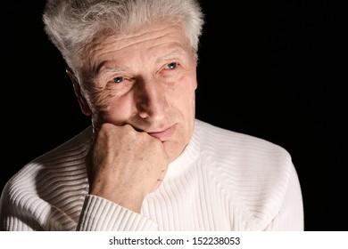 Portrait of a thoughtful elderly man against black background