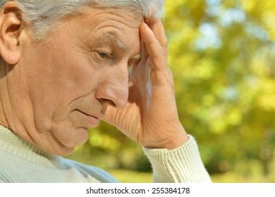 Portrait of thoughtful elderly man on yellow autumn background