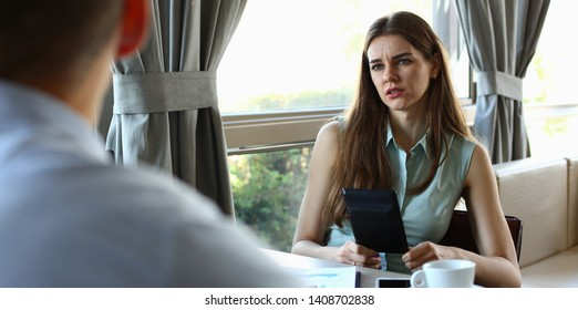 Portrait of thoughtful female discussing important business topic with friendly colleagues. Moody woman holding calculator and looking at company workers. Restaurant interior