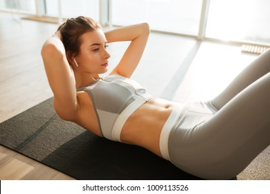 Portrait of thoughtful girl in sporty top and leggings lying on yoga mat and rock press while listening music in earphones at home with big windows on background
