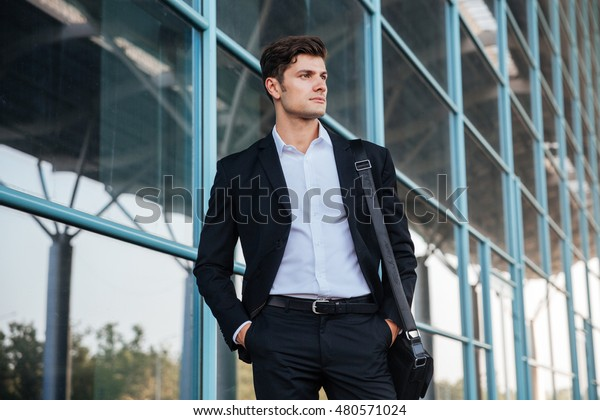 Portrait of a thoughtful handsome businessman standing on the street