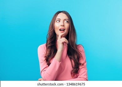 Portrait of thoughtful happy woman looking sideways isolated on blue background. Doubt concept