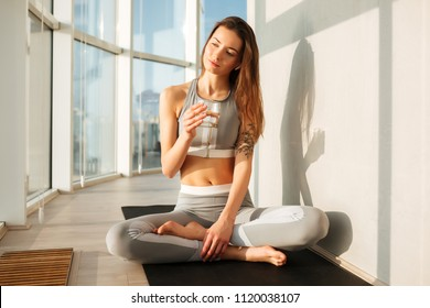 Portrait of thoughtful lady in sporty top and leggings sitting in lotus pose on yoga mat and drinking pure water at home with big beautiful windows on background