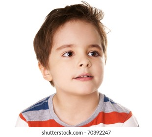 Portrait of thoughtful little smiling boy looking up on white background