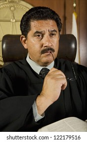 Portrait of thoughtful male judge sitting with book in courtroom