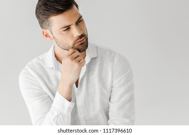 portrait of thoughtful man in linen white shirt looking away isolated on grey background