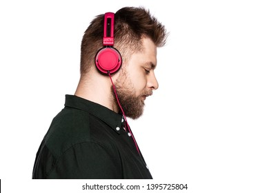 Portrait of thoughtful man looking down. Model showing only right side of unshaved face. Bearded guy wearing red headphones and black shirt. Isolated on white
