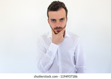 Portrait of thoughtful office worker holding chin and looking at camera. Handsome stylish pensive man thinking isolated on white. Concentration concept