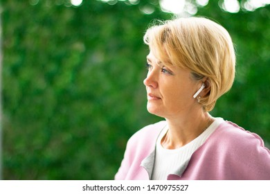 Portrait of a thoughtful pensive elderly adult woman looking into the distance with a sad look and listening to music in wireless earphones. Green natural background. Side view. Middle aged female.