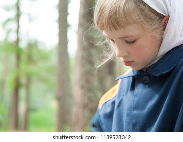 Portrait of a thoughtful preschooler girl outdoors