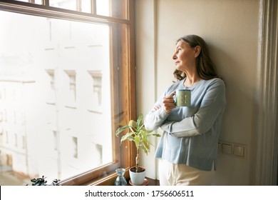 Portrait of thoughtful retired mature woman in casual clothes standing by large window, leaning on white wall, looking outside, drinking tea. People, social distancing and quarantine concept