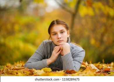 Portrait of a thoughtful and sad girl with red hair looking at the camera, lying on the yellowing leaves, against the background of the autumn park. Autumn colors . Lifestyle. Autumn mood. Forest