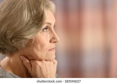 Portrait of thoughtful sad nice elderly woman