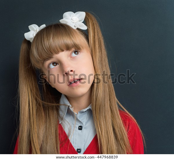 Portrait of thoughtful schoolgirl at the black chalkboard in classroom. Back to school concept.