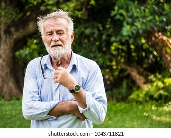 Portrait of Thoughtful senior man in a park.
