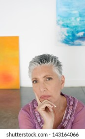 Portrait of thoughtful senior woman with hand on chin in art gallery
