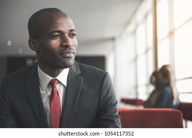 Portrait of thoughtful stylish man sitting in spacious room, looking aside. Women on background. Copy space in right side