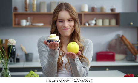 Portrait of thoughtful woman choosing between healthy food and unhealthy food in kitchen. Closeup of smiling girl looking at dessert and apple indoors. Emotional woman preferring fresh fruit