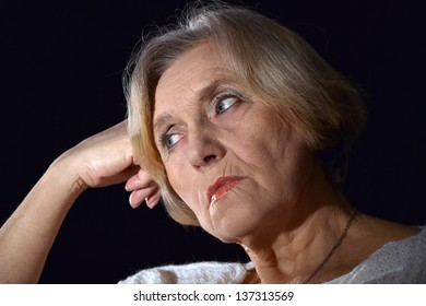 portrait of thoughtful woman in white on a black background