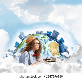 Portrait of thoughtful woman writer looking away and using typing machine while sitting at the table with flying papers and Earth globe among cloudy skyscape on background. Elements of this image