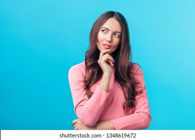 Portrait of thoughtful wondering woman looking sideways isolated over blue background. Doubt concept