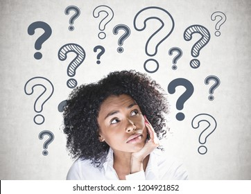 Portrait of thoughtful young african american woman with curly black hair looking up with her hand on the chin. Concrete wall background with many question marks on it.