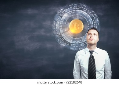 Portrait of thoughtful young businessman standing on chalkboard wall background with copy space and bitcoin hologram. Cryptocurrency concept