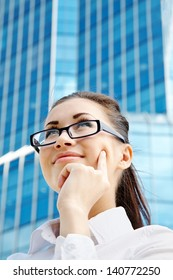 Portrait of thoughtful young businesswoman over office building