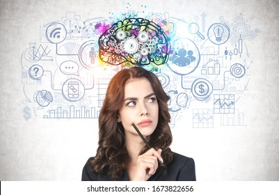 Portrait of thoughtful young businesswoman with pencil and long wavy hair standing near concrete wall with colorful brain sketch and business icons drawn on it. Concept of planning