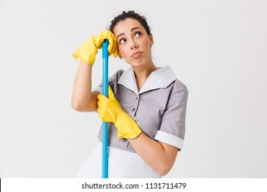 Portrait of a thoughtful young housemaid dressed in uniform leaning on a mop isolated over white background