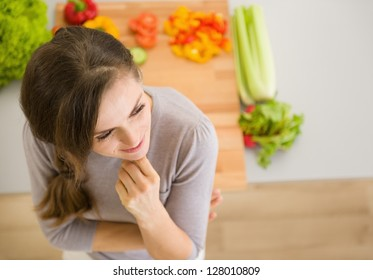 Portrait of thoughtful young woman in kitchen