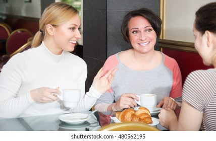 Portrait of three adult happy woman sitting in the cafe and talking with each other